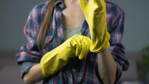 Determined wife ready to start cleaning the household, puts on yellow gloves Live Action