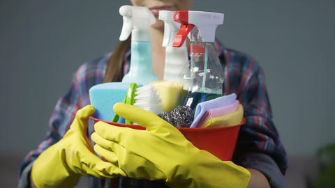 Smiling woman lifting up bucket with numerous household cleaning substances Footage