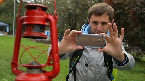 Curious backpacker making photos of rare kerosene lamp on his modern smartphone Live Action