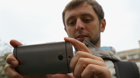 Male tourist looking at application with tourist itinerary on his smartphone Footage