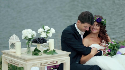 Just Married Couple Sitting Embraced Near a Pond Footage
