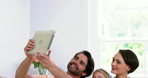 Cute family smiling and taking a photo with a tablet Live Action