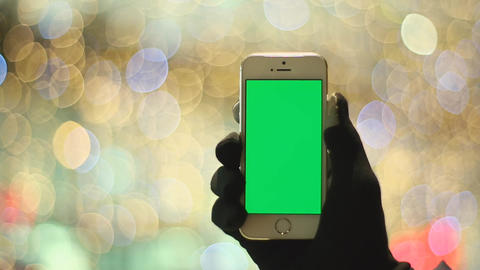Man Using Smartphone With Green Screen in Background Light. Easy for Cut and Key Footage