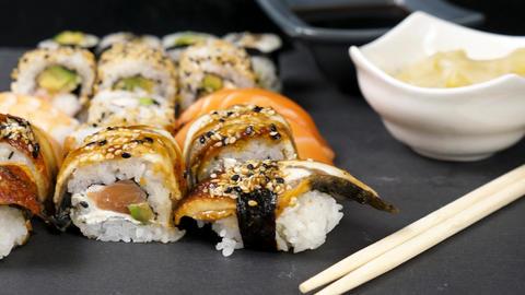 Mix variety of sushi rolls on black stone background Footage