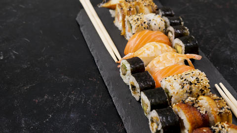 Rolls of traditional sushi on black stone plate Footage
