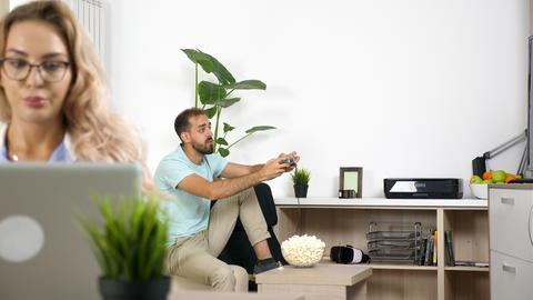 Noisy boyfriend plays video game while freelancer girlfriend is working at home Live Action