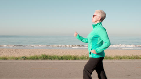 Senior Woman Exercising At The Beach GIF