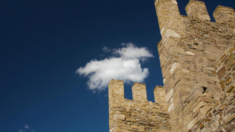 Old massonary of the medeival fortress tower in background of blue skies with Live Action