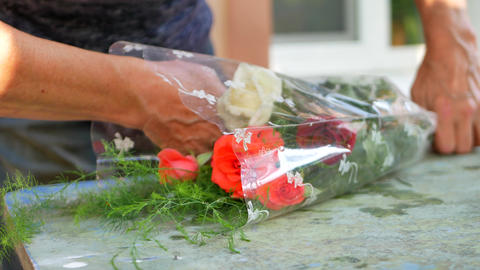 Woman florist's hands making bouquet with roses on table for flower shop Footage