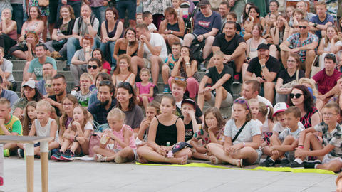 A Crowd of People Sitting on the Ground in Town Live Action