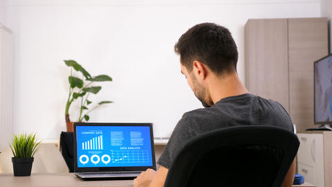 Businessman at home in casual clothes looking on computer screen with animated Footage