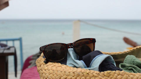sunglasses placed in a basket on the beach Live Action