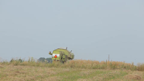 Combine green standing in a field Live Action