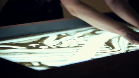 Artist Draws Two People on Sand Footage