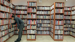 Man Coming to the Book Shelf and Pulls out a General Plan Footage