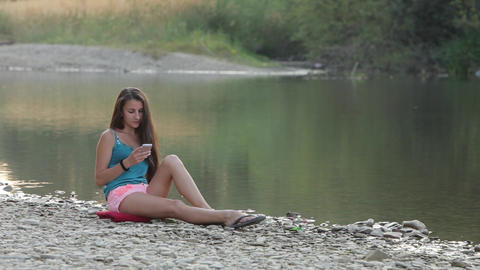 Girl Sitting on the River Bank With the Phone, the Phone Picks Footage