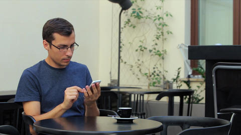A Man Sits at a Table in the Cafe and Uses the Phone Footage