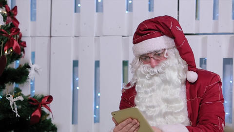Santa Claus Buy and Pay on Digital Tablet in Room with Christmas Tree and Gifts Footage