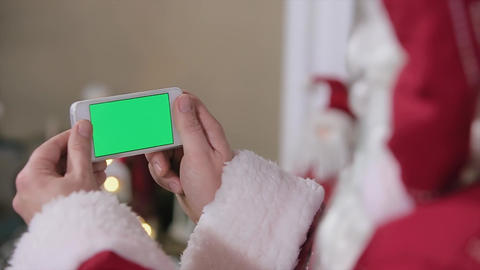 Santa Hold Phone in Hands Chroma Key. Phone with Green Screen in Landscape Mode. Footage