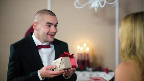 Woman in Evening Black Dress Giving Gift to Man in a black suit with a red ribbo Footage