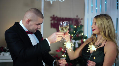 Happy Man in Suit and Woman in Evening Dress knocking glasses in a white room wi Footage