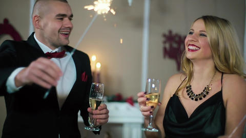 Happy Man in Suit and Woman in Evening Dress knocking glasses burn berals lights Footage