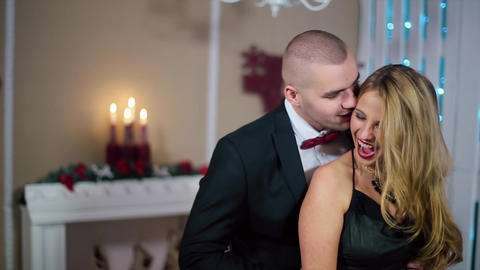 a Man in a Black Suit Kissing a Woman in Evening black dress, wide smile, happin Footage
