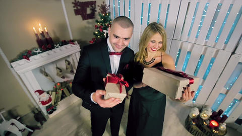 Happy Man And Woman Dressed in Evening Dress presenting gifts in a white room wi Live Action