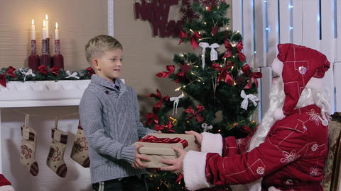 Santa Showing Thumbs Up Gives a Gift to the Little Boy, the Boy Shakes the Box Footage
