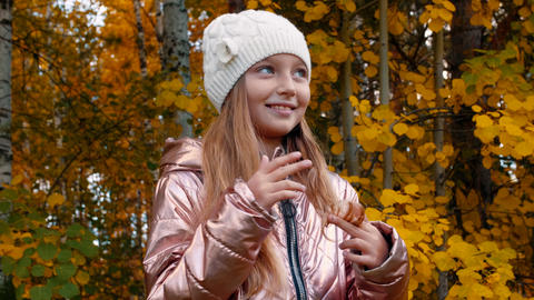 Portrait cute girl touching long hair and looking to camera in autumn forest Footage