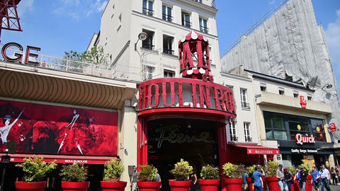 Paris, France - July 07, 2018: World famous Moulin Rouge on a cloudy day Live Action