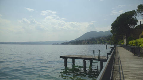 Stunning view of wooden pier on lake Garda and Monte Baldo mountains, landscape Live Action