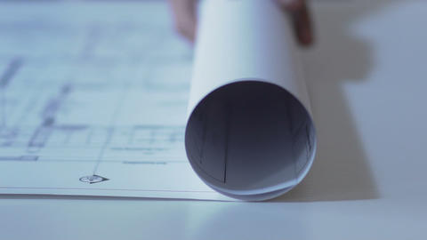 Designer unrolling building guidelines drawing on table, architecture design Footage