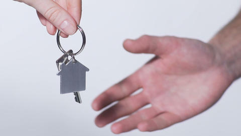 Woman handing over a key from new apartment to man, quick deal on house rent Live Action