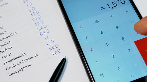 Home budget planning with pen and smartphone calculator Live Action