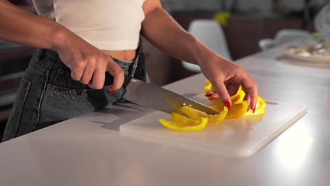 Sexy woman cuts the yellow pepper with the sharp knife on the board, woman cooks Live Action