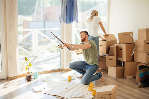 couple is having fun in home with cardboard boxes in new house at moving day Photo