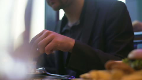 Hungry man eating french fries dipping it into sauce, quick snack in cafe Footage