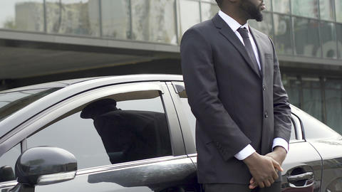 Private driver and bodyguard standing near car waiting for rich vip client Live Action
