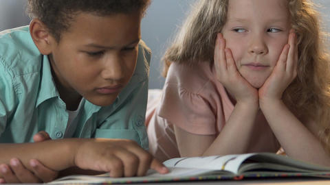 Kids lying next to each other, boy reading book, exchanging looks, friendship Live Action