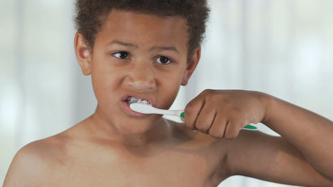 Mixed-race boy brushing teeth, dental hygiene healthy habits, mirror reflection Live Action