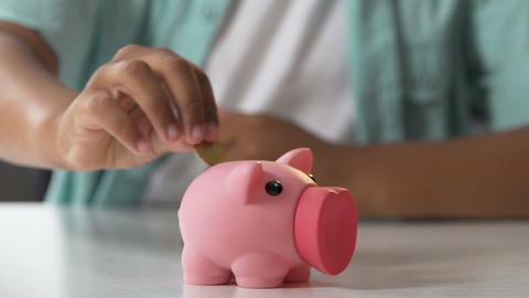 Kid putting coin in piggy bank, saving pocket money, financial literacy for kids Footage