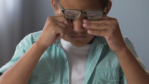 Little biracial boy in glasses doing homework, rubbing eyes, strained eyesight Live Action