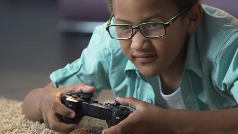 Addicted kid on floor rubbing eyes and playing video games on play station Footage