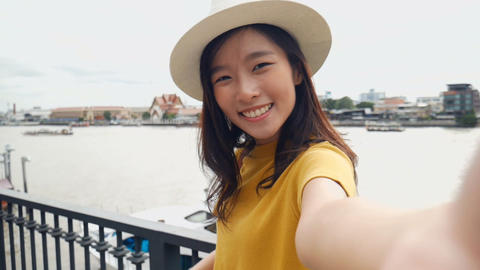 Beautiful asian woman taking selfies on a smartphone. Young asian girl tourist Live Action