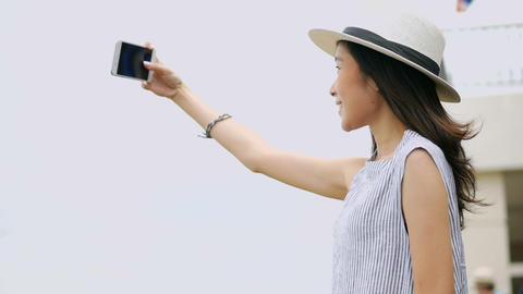 Beautiful asian woman taking selfies on a smartphone. Young asian girl smiling Live Action