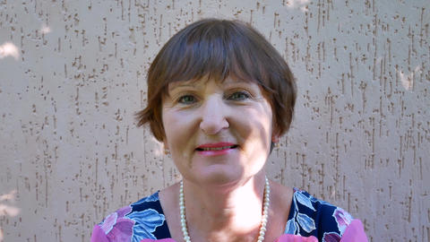 Portrait of senior woman with brown hair GIF