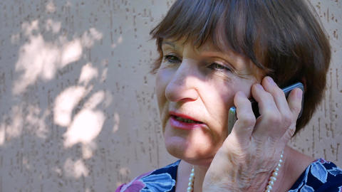 Senior woman talking on phone outside near home GIF