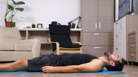 Man lying down on a blue mat on his living room Footage