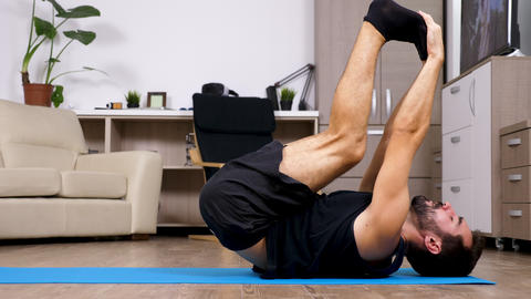 Young fit man on the floor in his living room does different yoga poses Footage